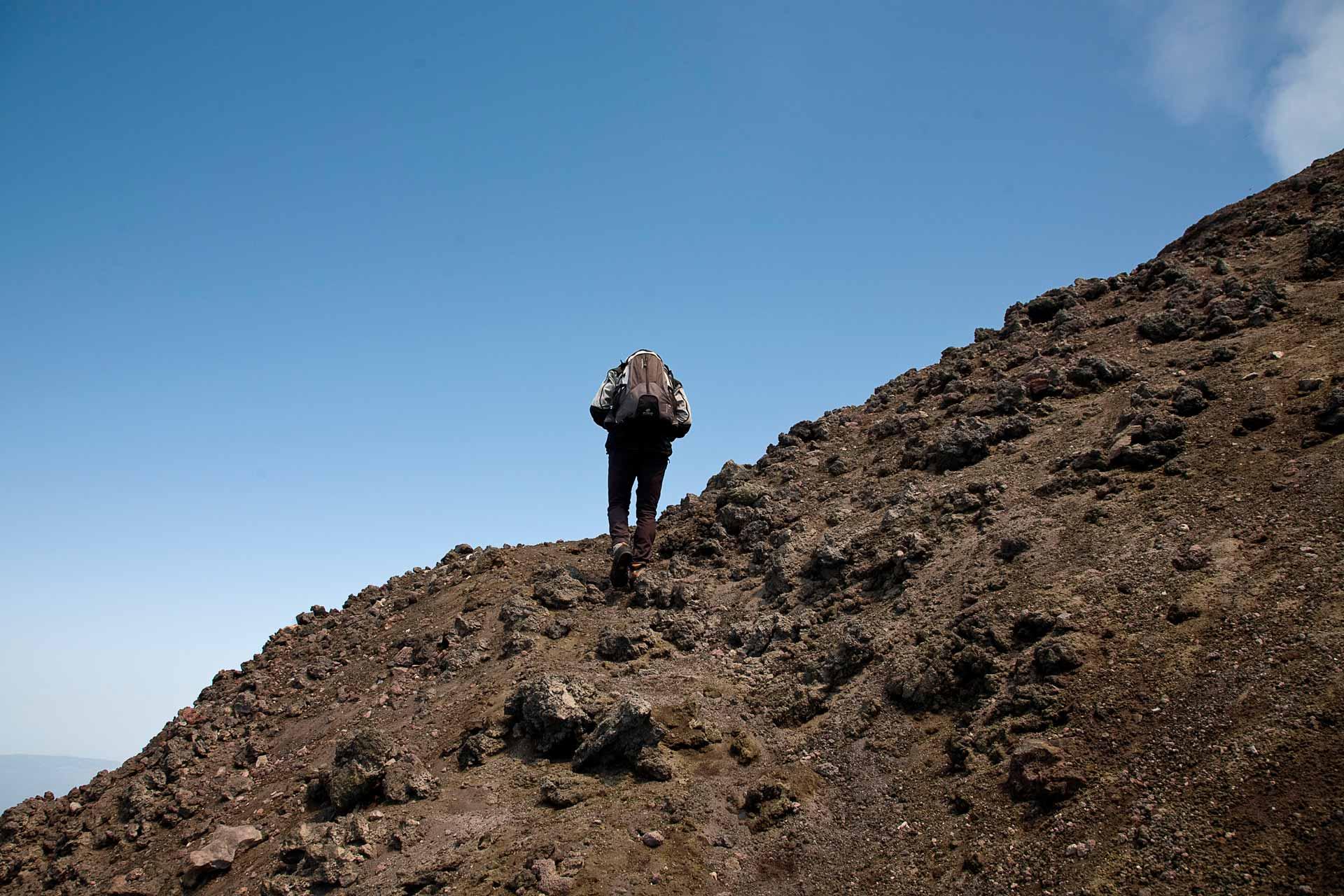 Continuiamo la salita sul costone sud-ovest del vulcano, i coni neri dei crateri avventizi, che incontriamo lungo il percorso, sono le sinistre vestigia di terribili e recenti eruzioni laterali. L?area craterica sommitale non rimane mai uguale nel tempo, anzi, si trasforma continuamente. Basti pensare che solo centoventi anni fa la cima del vulcano culminava con un unico Cratere Centrale, mentre oggi ne troviamo ben quattro, a riprova di rapidi e marcati cambiamenti morfo-strutturali.