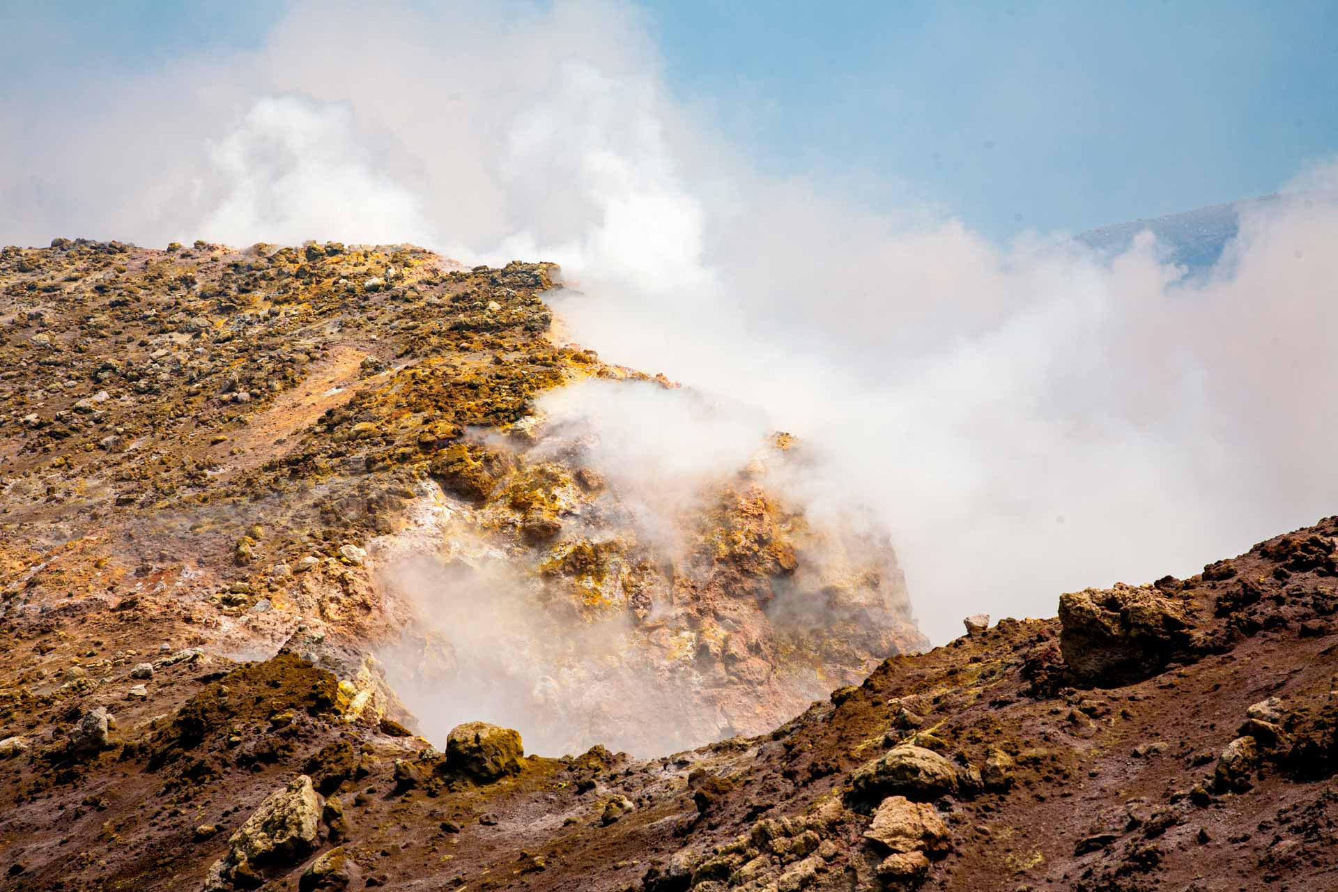 """Continuing in a threatening atmosphere of mephitic clouds, a frightening abyss opens on the west side: the """"New Bocca"""". Still active today, the crater is still growing larger. Its 300 meters wide shaft encloses many eruptive vents in its smoky depths. The fumes that come out millions of cubic meters from the crater chimney consist of water vapor, acids and gases such as hydrogen sulfide, carbon dioxide and hydrochloric acid and many other equally unbreathable and corrosive components."""