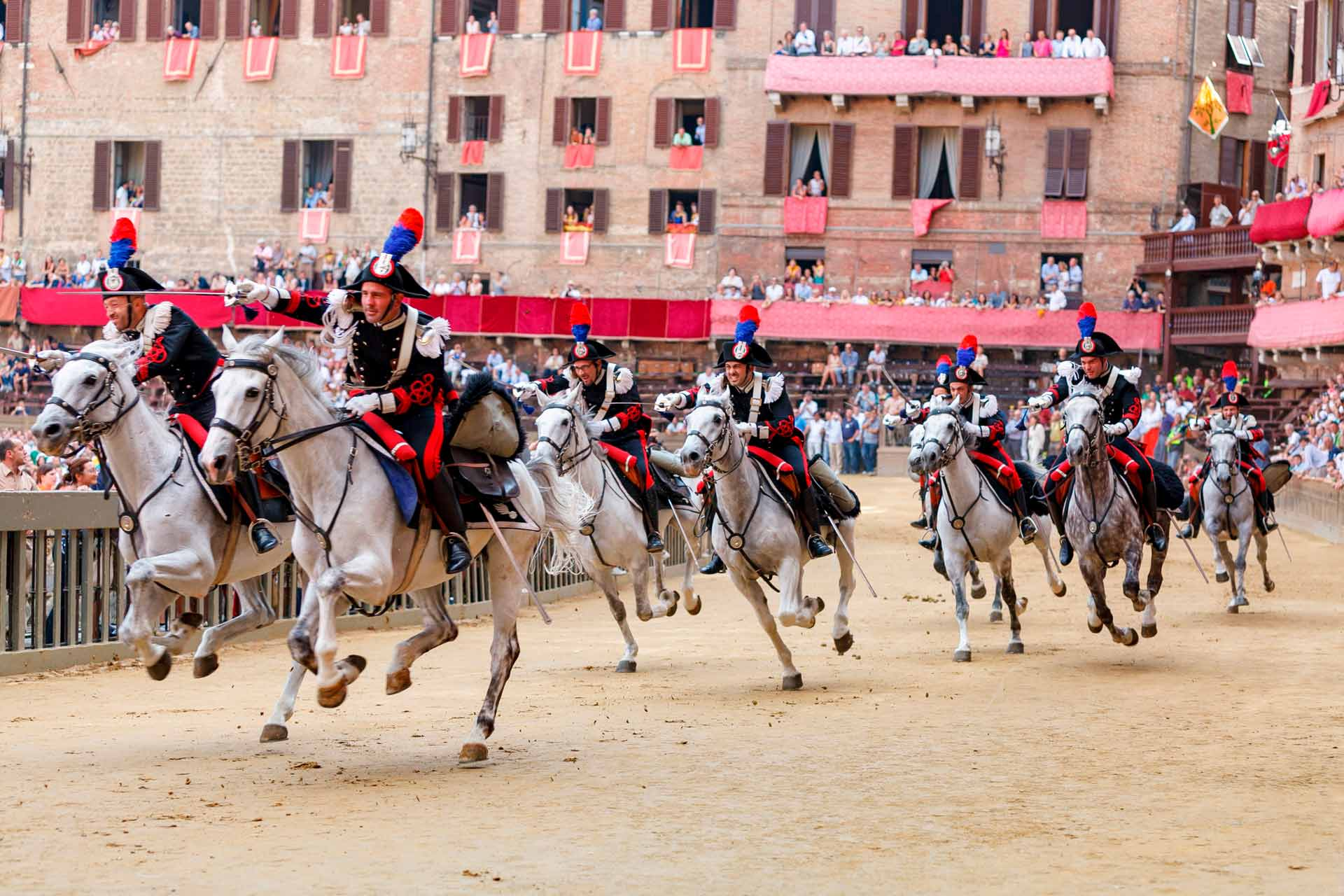 """ON TRACK FOR THE""""CARRIERA"""" - In the afternoon the square begins to fill up, the Carabinieri of the 4th Regiment on horseback from Rome enter the track, do a lap of honor and then perform in a splendid charge with unsheathed swords, preceding the walk of the Historical Parade."""